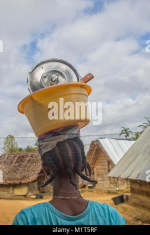 Maroon woman carrying bowl with dishes on her head in Botopasi, Marowijne area in Suriname - Stock Photo