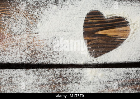 Heart of white flour on a wooden board. Cooking with love. Holiday backing background. Eco food and home cooking. - Stock Photo