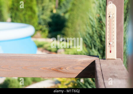 Wooden garden thermometer on a street in a country house - Stock Photo