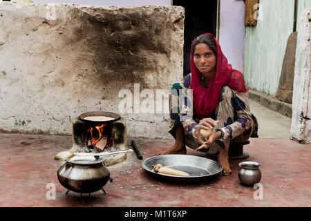 Jaipur,India-March 9, 2107: Unidentified Indian woman prepare food in a small courtyard of her house. - Stock Photo