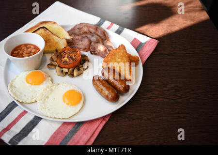 traditional full English breakfast served and ready to eat with fried eggs sausages mushrooms bacon beans toast - Stock Photo