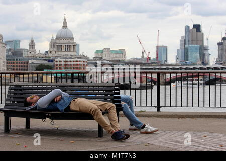 London, United Kingdom - August 24 2017: Two young men in nice clothing and sunglasses recline on a bench in front - Stock Photo