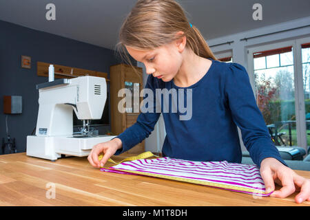 Portrait of a 8 year old girl measuring a pink and white striped cloth with a measuring tape - Stock Photo
