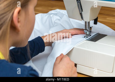 A 8 year old girl is sewing a white textil - Stock Photo