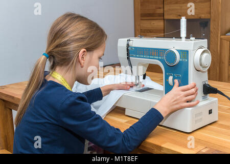 A 8 year old girl is sewing a white textile. Right hand presses the rewind button - Stock Photo
