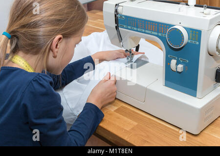 A 8 year old girl is sewing a white textile - Stock Photo