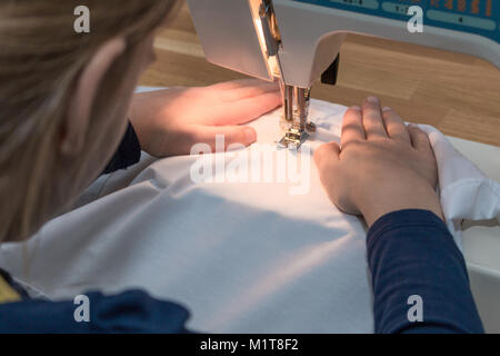 A 8 year old girl is sewing a white textile. Close-up - Stock Photo