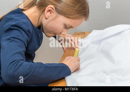 A 8 year old girl is measuring a white textile with a yellow measuring tape. Close-up - Stock Photo