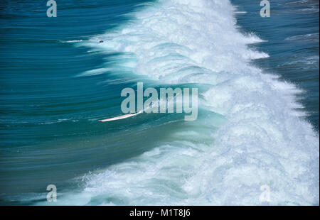 A surfer wiping out in the Pacific Ocean waves crashing down on Manhattan beach california on a sunny day on the - Stock Photo