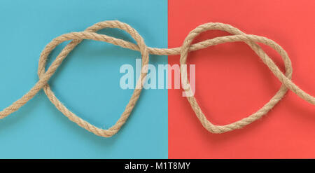 Two heart shapes from rope on blue and red background - Stock Photo
