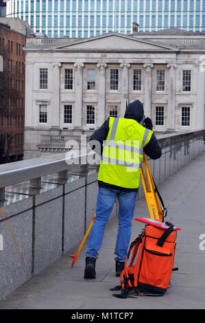 a construction worker or engineer measuring buildings and structures using a theodolite on a yellow tripod. A surveyor - Stock Photo
