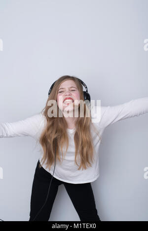 Girl singing with passion and eyes closed while listening to music with over-the-ear headphones on white background - Stock Photo
