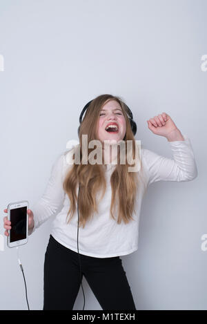 Girl singing with passion and eyes closed while listening to music on smartphone with over-the-ear headphones on - Stock Photo