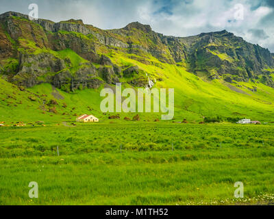 Typical icelandic summer landscape with mountain, waterfalls, green field, cows and barn - Stock Photo