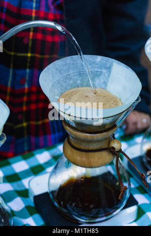 Barista pours boiling water fron specialized kettle on pour over coffee in artisan glass brewer while outdoors - Stock Photo