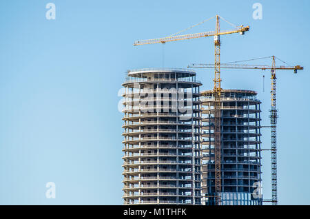 New buildings being constructed. Industrial building site. Shot of two lifting cranes and skyscrapers under construction - Stock Photo