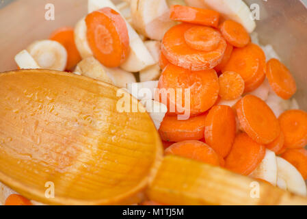 Natural wooden spoon in a bowl full of chopped vegetables - slices of carrot, pasternak and onions. Preparing soup - Stock Photo
