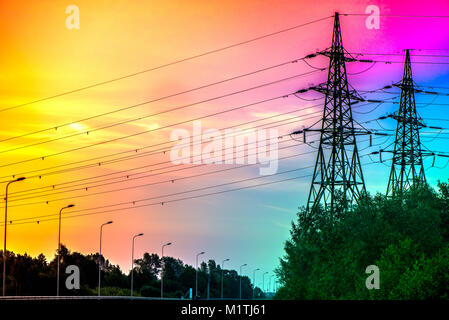 A silhouette of high voltage electrical tower structure next to highway road in early morning, during sunrise. Electricity - Stock Photo