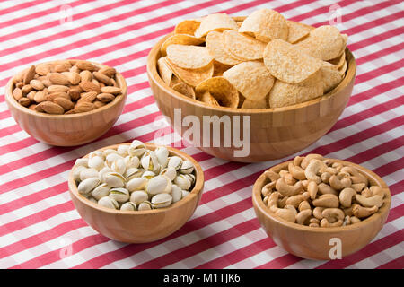 Close up of party bowls of potato chips, almonds, pistachios, and cashews on a red checkered tablecloth - Stock Photo