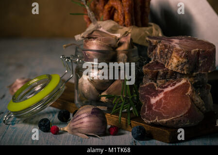 Horizontal photo of tuscany wild boar meat which is dried and smoked. Meat is cut to pieces and stacked on wooden - Stock Photo