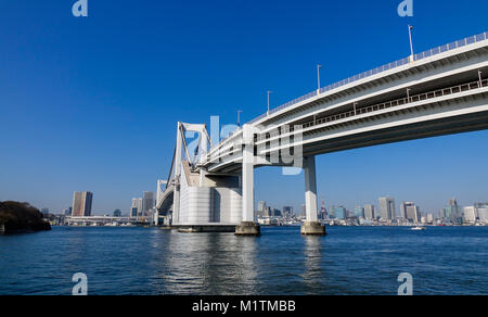 View of Rainbow Bridge on Tokyo Bay, Japan. The bay is inlet of the Pacific Ocean on the east-central coast of east - Stock Photo