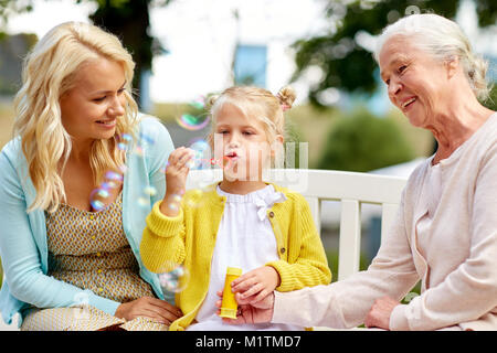happy family blowing soap bubbles at park - Stock Photo