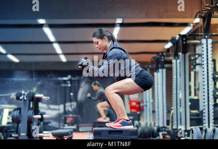 woman doing squats on platform in gym - Stock Photo