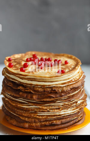 High stack of classic Russian thin pancakes with red currant berries . Rustic style. Traditional for the Russian - Stock Photo