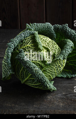 Savoy cabbage on a dark wooden table. - Stock Photo