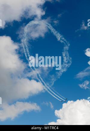 Aerobatic maneuver in a blue sky - Stock Photo