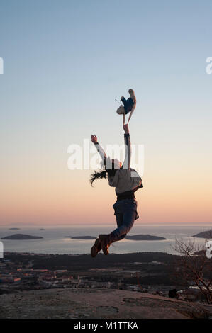 girl jumping on the hill reaching the sky - Stock Photo