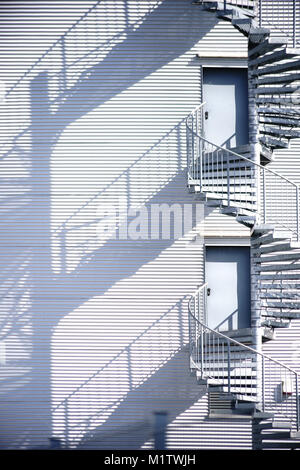 A spiral staircase, fire escape on the side of a industrial building façade throws shadows. - Stock Photo