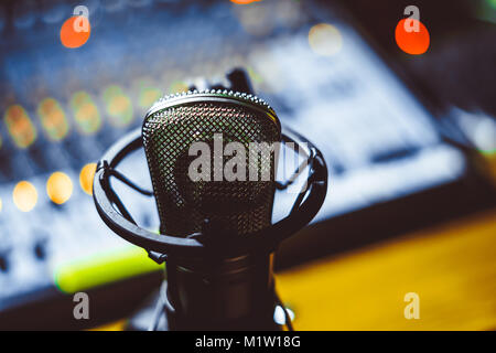Professional condenser studio microphone over the musician blurred background and audio mixer, Musical instrument - Stock Photo