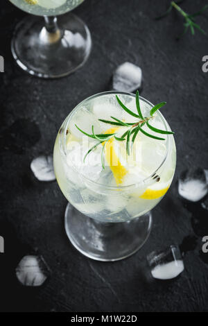 Alcohol drink (gin tonic cocktail) with lemon, rosemary and ice on rustic black stone table, copy space, top view. - Stock Photo