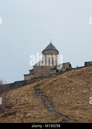 The Gergeti Trinity Church perched on a mountaintop at the elevation of 2170 meters in the High Caucasus Mountains - Stock Photo