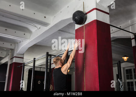 Young Male Athlete Doing Wall Balls Exercise At The Gym - Stock Photo