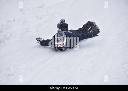 Little boy slides on snow in winter time - Stock Photo