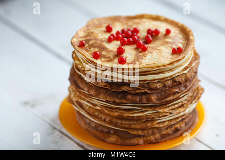 High stack of classic Russian thin pancakes with red currant. Rustic style. Traditional for the Russian pancake - Stock Photo