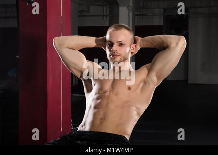 Portrait Of A Young Athlete Man Doing Stretching Exercise In The Gym - Stock Photo