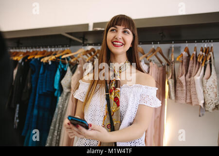 Happy customer entering pin on a point of sale machine at a fashion boutique. Variety of designer clothes on display - Stock Photo