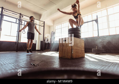 Fit young woman box jumping with man exercising with skipping ropes at a cross training style gym. Young couple - Stock Photo