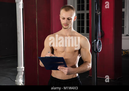 Portrait Of An Athlete Man Writing A Workout Plan On Clipboard In The Gym - Stock Photo