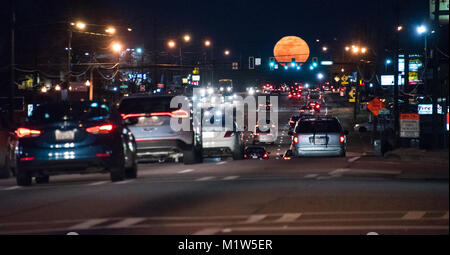 Metro Atlanta commuters in rush hour traffic as a full moon rises above US Highway 78 in Snellville, Georgia. (USA) - Stock Photo