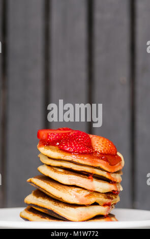 Delicious Strawberry Pancakes on a dark moody background, stunning breakfast with vibrant colors, white plate - Stock Photo