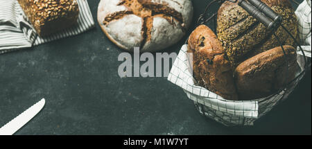 Various bread loaves on grey concrete background, copy space - Stock Photo
