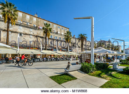 Sunny summer afternoon on the Riva Promenade at the Harbor of Split Croatia with tourists, bicyclist, palm trees - Stock Photo