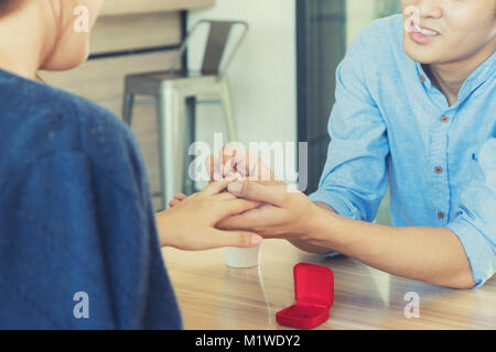 Asian handsome man putting wedding ring on and proposing to his beautiful woman in cafe. Love, anniversary, surprise, - Stock Photo