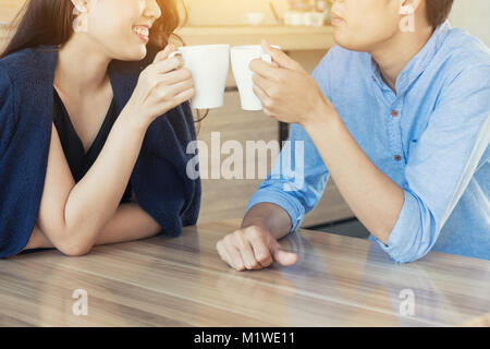Happy young couple people relaxing meeting and drinking tea or coffee in cafe. Looking happy dating. - Stock Photo