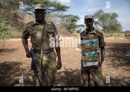 Karamoja, Uganda. 31st Jan, 2018. Ugandan police hold up a poster warning girls not to cross the border to Kenya - Stock Photo