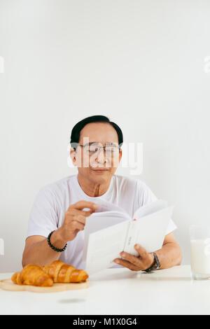 Happy senior couple having croissant and milk breakfast at home, reading book. - Stock Photo
